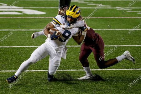 Michigan running back Chris Evans (9) breaks the tackle Minnesota defensive back Tyler Nubin (27) for a touchdown in the fourth quarter of an NCAA college football game, in Minneapolis. Michigan won 49-24