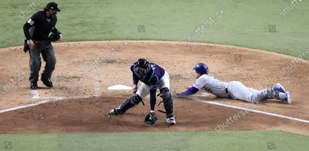 Los Angeles Dodgers baserunner Corey Seager (R) scores as Tampa Bay Rays catcher Mike Zunino (C) takes the throw on batter Max Muncy's RBI single  in the top of the fifth inning of Major League Baseball's World Series Game four at Globe Life Field in Arlington, Texas, USA, 24 October 2020.