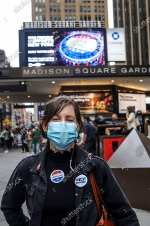 Stock Photo of Natalie Sheriden wears a #Vote RUTHlessly button in honor of Ruth Bader Ginsburg and waited 4 hours to cast her vote on the first day of early voting in New York City at Madison Square Garden, which was turned into a polling site for the first time