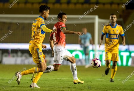 Diego Reyes (L) of Tigres in action agsinst Victor Manon (C) of FC Juarez during a Torneo Guardianes 2020 Liga MX championship soccer match between Tigres de Monterrey and FC Juarez, at the University Stadium in Monterrey, Mexico, 24 October 2020.