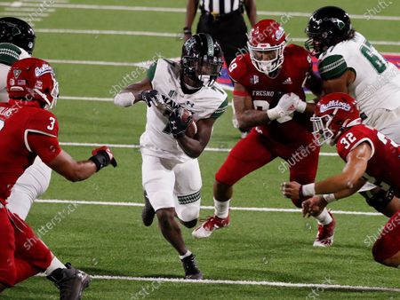 Stock Photo of Hawaii running back Calvin Turner runs past Fresno State defensive lineman Colby Warkentin and defensive back Evan Williams, right, during the second half of an NCAA college football game in Fresno, Calif
