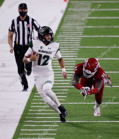 Hawaii quarterback Chevan Cordeiro (12) takes off for a big gain against Fresno State defensive end Andrew Wright during the second half of an NCAA college football game in Fresno, Calif