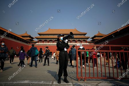 Security guard uses a loud speaker to advise tourists to scan their health code before entering Forbidden City in Beijing, . With the outbreak of COVID-19 largely under control within China's borders, the routines of normal daily life have begun to return for its citizens