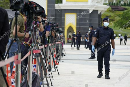 Police wearing a face mask to help curb the spread of the coronavirus guard media outside National Palace in Kuala Lumpur, Malaysia, . Malay rulers hold a special meeting on Sunday to discuss the government's plan to declare an emergency to tackle the worsening COVID-19 situation