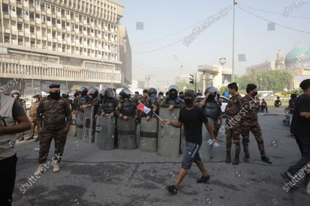 Anti-riot police forces stand guard as Iraqi protesters take part in a demonstration at the al-Khilani square in Baghdad, Iraq, 25 October 2020. A demonstration was held to mark the 25 October 2019 mass protests that resumed a day after some 50 protesters were killed and injured when attempting to enter Baghdad's heavily fortified 'Green Zone'.