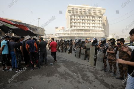 Anti-riot police forces stand guard as Iraqi protesters take part in a demonstration at the al-Khilani square in Baghdad, Iraq, 25 October 2020. A demonstration was held to mark the 25 October 2019 mass protests that resumed a day after some 50 protesters were killed and injured when attempting to enter Baghdad's heavily fortified 'Green Zone', and demand to put those on trial who are responisble for the killed protesters.