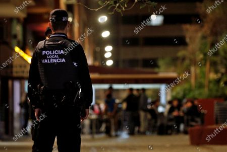 A local policeman stands guard next to a bar before a curfew was imposed at a bars and restaurants district in Valencia, Spain, early 25 October 2020. Curfew was imposed in the region since last night, from midnight to 6 am, amid other measures, to try to avoid the spreading of COVID-19 virus disease.