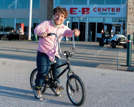 Stock Photo of Comedian Nic Novicki rides his bike in the parking lot