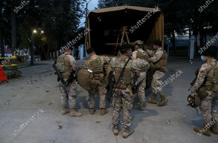 Military members arrive to guard a polling station during a referendum to decide whether the country should replace its 40-year-old constitution, in Santiago, Chile