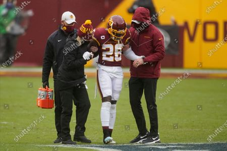 Washington Football Team strong safety Landon Collins (26) is helped off the field after suffering an ankle injury in the first half of an NFL football game against the Dallas Cowboys, in Landover, Md