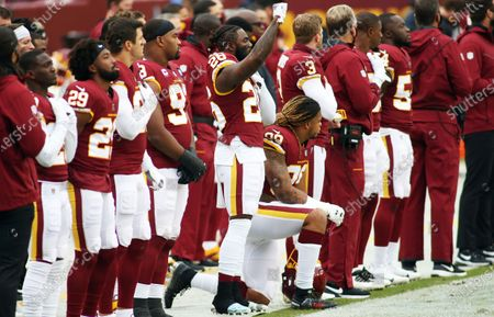 Stock Photo of Washington Football Team strong safety Landon Collins (26)raises his fist during the playing of the National Anthem before an NFL football game against the Dallas Cowboys, in Landover, Md