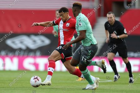 Southampton's Che Adams, controls the ball under pressure from Everton's Yerry Mina during an English Premier League soccer match between Southampton and Everton at the St. Mary's stadium in Southampton, England