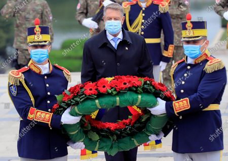 Romanian honor guard soldiers carry a wreath of flowers as Romanian President Klaus Iohannis (C) follows them in order to pay respect for the fallen heroes at the Unknown Soldier Memorial, during the Romanian Army Day celebration, in Bucharest, Romania, 25 October 2020. The Armed Forces Day in Romania is marked to commemorate retaking Carei, the last Romanian city under joint German-Hungarian occupation on 25 October 1944.