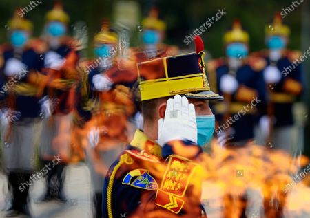 A Romanian honor guard soldier wearing a protective mask stands at attention, as seen through the eternal flame, at the Unknown Soldier Memorial, during the Romanian Army Day celebration, in Bucharest, Romania, 25 October 2020. The Armed Forces Day in Romania is marked to commemorate retaking Carei, the last Romanian city under joint German-Hungarian occupation on 25 October 1944.