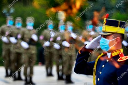 A Romanian honor guard soldier that wears a protective mask stands at attention, as seen through the eternal flame, at the Unknown Soldier Memorial, during the Romanian Army Day celebration, in Bucharest, Romania, 25 October 2020. The Armed Forces Day in Romania is marked to commemorate retaking Carei, the last Romanian city under joint German-Hungarian occupation on 25 October 1944.