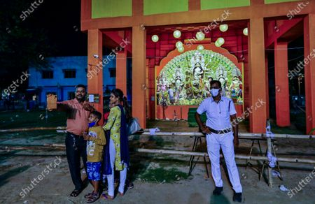 An Indian family takes photo on their mobile phone as a policeman stands guard near a deserted worship venue of Durga Puja, the biggest festival of the region, in Kolkata, India, . The Hindu festival season is traditionally laced with an unmatched fanfare and extravaganza, with socializing being the hallmark of the celebration. But because of the coronavirus pandemic this year's festivities have started on a pale note