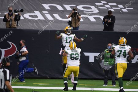 Green Bay Packers wide receiver Davante Adams (17) celebrates with teammate Lucas Patrick (62) after catching a 3-yard touchdown pass during the first half of an NFL football game against the Houston Texans, in Houston