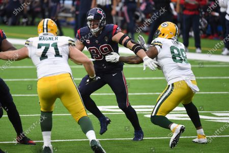 Houston Texans defensive end J.J. Watt, center, rushes up field between Green Bay Packers offensive tackle Rick Wagner (71) and tight end Marcedes Lewis, right,during the first half of an NFL football game, in Houston