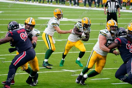 Green Bay Packers quarterback Aaron Rodgers hands the ball off to running back Jamaal Williams (30) during the second half of an NFL football game against the Houston Texans, in Houston