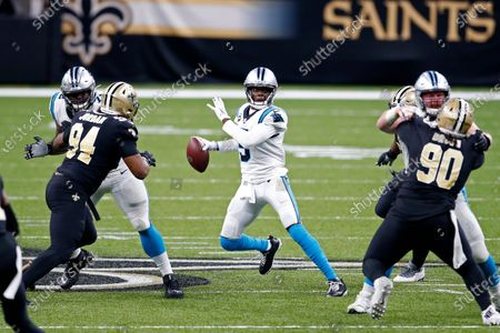 Stock Picture of Carolina Panthers quarterback Teddy Bridgewater scrambles under pressure from New Orleans Saints defensive end Cameron Jordan (94) and defensive tackle Malcom Brown (90) in the second half of an NFL football game in New Orleans