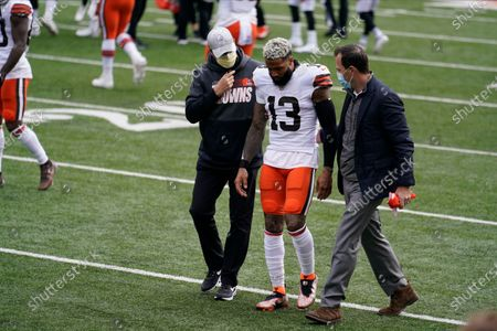 Cleveland Browns' Odell Beckham Jr. (13) is helped off the field during the first half of an NFL football game against the Cincinnati Bengals, in Cincinnati