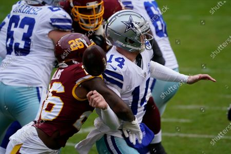 Stock Image of Washington Football Team strong safety Landon Collins (26) knocks the ball of the hands of Dallas Cowboys quarterback Andy Dalton (14) during the first half of an NFL football game, in Landover, Md