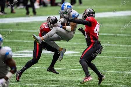 Detroit Lions wide receiver Kenny Golladay (19) catches a pass as Atlanta Falcons defensive back Kendall Sheffield (20) and linebacker Deion Jones (45) defend during the first half of an NFL football game, in Atlanta
