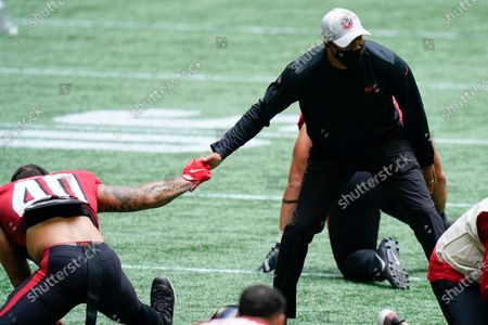 Atlanta Falcons head coach Raheem Morris speaks with Atlanta Falcons fullback Keith Smith (40) before the first half of an NFL football game between the Atlanta Falcons and the Detroit Lions, in Atlanta