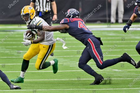 Green Bay Packers running back Jamaal Williams (30) runs with the ball as Houston Texans linebacker Zach Cunningham (41) defends during the second half of an NFL football game, in Houston