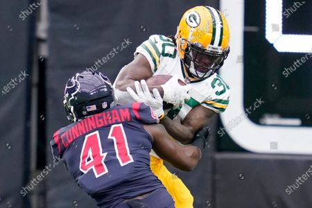 Green Bay Packers running back Jamaal Williams (30) runs for a short gain as Houston Texans linebacker Zach Cunningham (41) defends during the first half of an NFL football game, in Houston