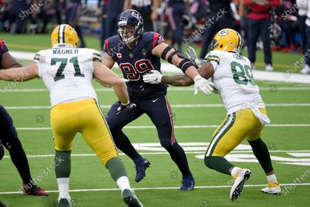 Houston Texans defensive end J.J. Watt (99) tries to get past Green Bay Packers offensive tackle Rick Wagner (71) and tight end Marcedes Lewis (89) during the first half of an NFL football game, in Houston
