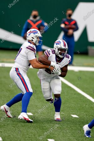 Buffalo Bills quarterback Josh Allen (17) hands the ball to Buffalo Bills running back Zack Moss (20) during an NFL football game against the New York Jets, in East Rutherford, N.J