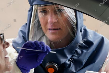 Salt Lake County Health Department public health nurse Lee Cherie Booth performs a coronavirus test outside the Salt Lake County Health Department in Salt Lake City. About half of U.S. states have seen their highest daily infection numbers so far at some point in October, and the country came very close to back-to-back record daily infection rates last week