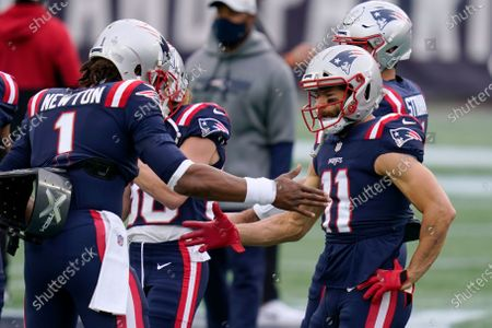 New England Patriots quarterback Cam Newton, left, slaps hands with wide receiver Julian Edelman before an NFL football game against the San Francisco 49ers, in Foxborough, Mass