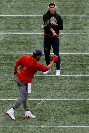 New England Patriots quarterback Jarrett Stidham, rear, tosses the football to wide receiver Julian Edelman as they warm up before an NFL football game against the San Francisco 49ers, in Foxborough, Mass