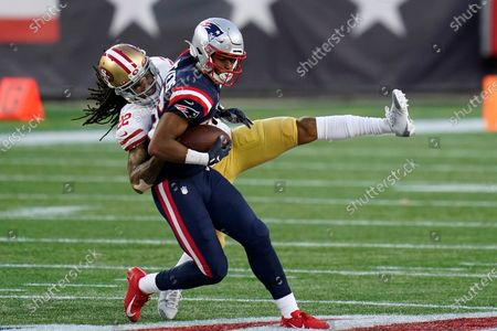 New England Patriots wide receiver Jakobi Meyers, right, is tackled by San Francisco 49ers cornerback Jason Verrett, rear, after catching a pass in the first half of an NFL football game, in Foxborough, Mass