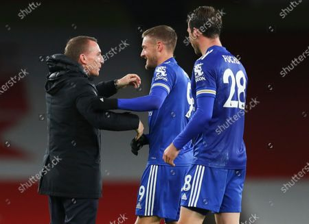 Leicester's manager Brendan Rodgers, left, embraces Jamie Vardy as Christian Fuchs, right, watches following the English Premier League soccer match between Arsenal and Leicester City at Emirates Stadium in London, England