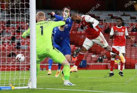 Stock Photo of Arsenal's Alexandre Lacazette, right, attempts to head the ball at the goal as Leicester's goalkeeper Kasper Schmeichel, left, and Christian Fuchs contest during the English Premier League soccer match between Arsenal and Leicester City at Emirates Stadium in London, England