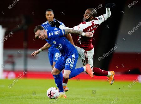 Leicester's James Maddison, left, and Arsenal's Alexandre Lacazette battle for the ball during the English Premier League soccer match between Arsenal and Leicester City at Emirates Stadium in London, England