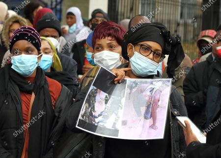 Protesters wearing face masks display placards during the rally. Guineans in UK protest outside Downing Street after Guinea President Alpha Conde was re-elected with opposition claims that the election was rigged.
