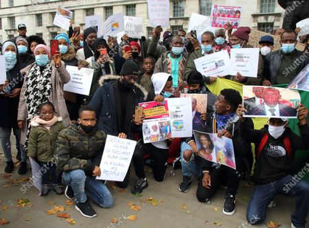 Protesters wearing facemasks hold up placards and portraits of claimed victims of the regime during the rally. Guineans in UK protest outside Downing Street after Guinea President Alpha Conde was re-elected with opposition claims that the  election was rigged.