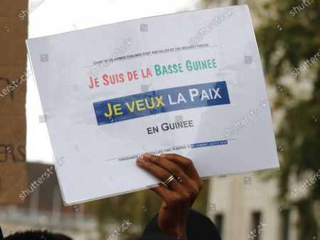 A protest placard is held in the air during the rally. Guineans in UK protest outside Downing Street after Guinea President Alpha Conde was re-elected with opposition claims that the election was rigged.