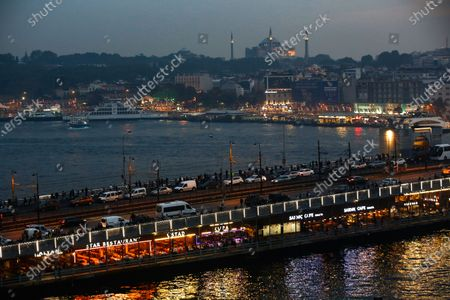 Backdropped by the Hagia Sophia in the distance, people walk on the Galata Bridge, over the Golden Horn in Istanbul