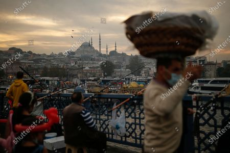 Backdropped by the Suleymaniye Mosque, people fish on the Galata Bridge over the Golden Horn in Istanbul