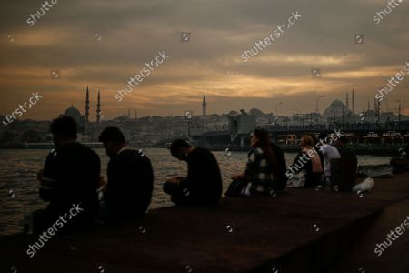 People sit on the promenade, by the Golden Horn in Istanbul