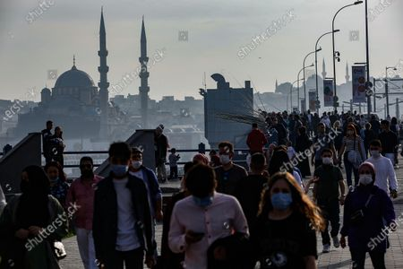 Backdropped by Yeni Cami (New Mosque), people walk on the Galata Bridge, over the Golden Horn in Istanbul
