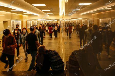 People walk through an underpass of the Galata Bridge, in Istanbul