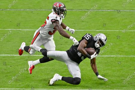 Las Vegas Raiders wide receiver Nelson Agholor (15) catches a pass over Tampa Bay Buccaneers cornerback Jamel Dean (35) during the second half of an NFL football game, in Las Vegas