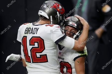 Tampa Bay Buccaneers quarterback Tom Brady (12) celebrates after making a touchdown pass to wide receiver Scott Miller, right, during the first half of an NFL football game, in Las Vegas