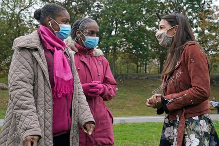 Rep. Alexandria Ocasio-Cortez, (D-N.Y.), right, talks with sisters Syria Carrington, left, and Libya Roberts who turned to meet the congresswoman at a Pledge to Vote event, in the Bronx borough of New York. Ocasio-Cortez is running for reelection in New York's 14th congressional district